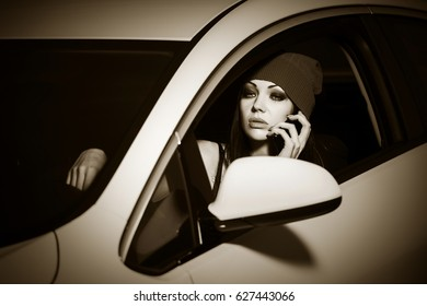 Young woman calling on cell phone in a car. Stylish fashion model outdoor
