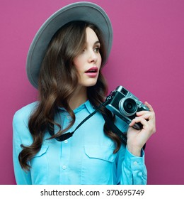 Uma jovem com câmera. Morena de camisa azul. Menina fotógrafa de moda hipster. Jovens, cultura juvenil