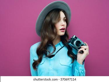 Junge Frau mit Kamera. Brunette in einem blauen Hemd. Hipster Modefotograf Mädchen. Jugendliche, Jugendkultur