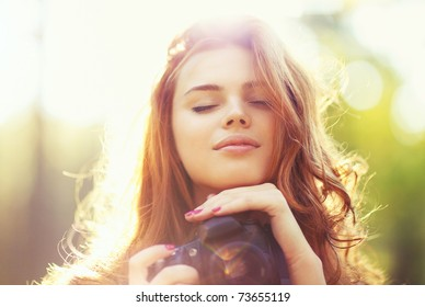 Young woman with camera outdoors portrait. Soft sunny colors.