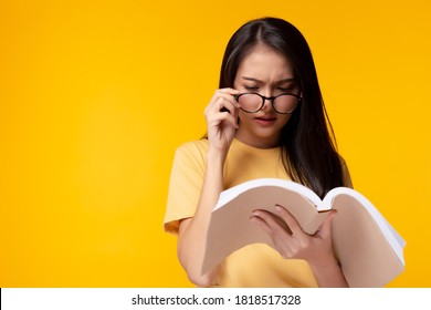 Young woman can not read book because her eyesight's getting worse. Young Asian girl wears eyeglasses and holding text book. She is university student. Isolated on yellow background, copy space