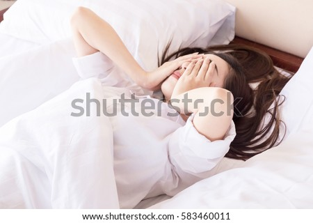 Young woman can not sleep. on her bed and thinking