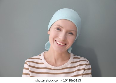 Young woman with cancer in headscarf on grey background