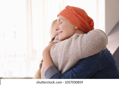 Young woman with cancer hugging her mother indoors