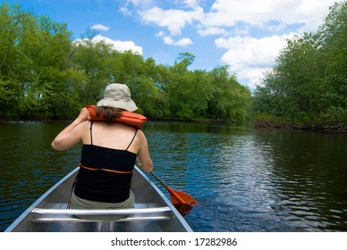 Young woman canoeing on an idyllic river