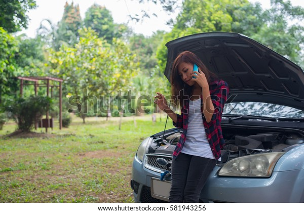 Young woman with car breaks down and she is calling the emergency services.