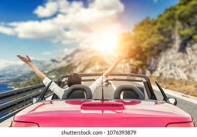 Young woman in a car with a convertible on the road to the sea against a backdrop of beautiful mountains on a sunny day. A woman raises her arms up.
