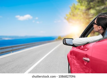 Young woman in a car with a convertible on the road to the sea against a backdrop of beautiful trees on a sunny day.