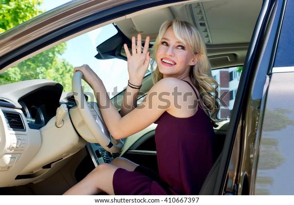 young woman in the car driver seat having fun