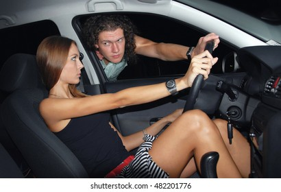 Young woman in the car and a man squeezed through the window and grabbed the steering wheel