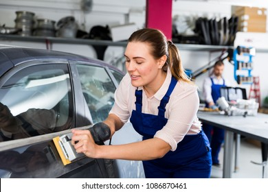 Young woman car mechanic in workshop sanding automobile body, preparing for painting