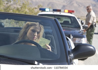 Young woman in car reading ticket with traffic cop in the background