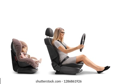 Young woman in a car seat holing a steering wheel and a baby girl strapped in a car seat isolated on white background