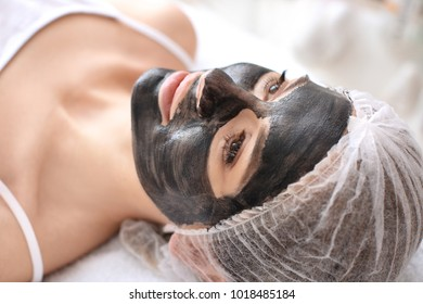 Young woman with carbon nanogel on her face in salon. Peeling procedure