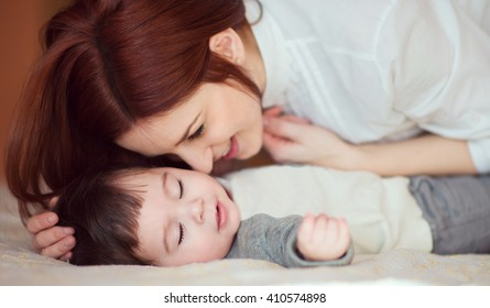 Young woman caressing her newborn baby who is asleep. Sweet moment