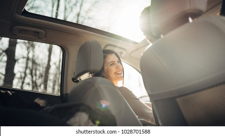 Young woman in a car,female driver looking at the passenger and smiling.Enjoying the ride,traveling,road trip concept.Driver feeling happy and safe.Learning how to drive,getting drivers licence.