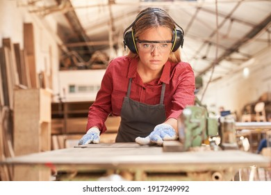 Young woman as a carpenter with safety glasses and hearing protection works on planing machine
