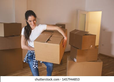 Young woman carrying big cardboard full of home essentials into a new home.Moving house.