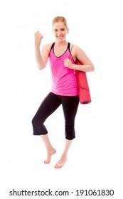Young woman carrying exercising mat and celebrating success