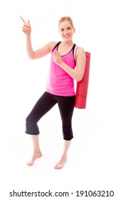 Young woman carrying exercising mat pointing and smiling