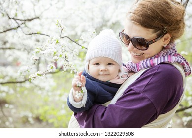 Young woman carrying her baby daughter in woven wrap outdoors in spring park