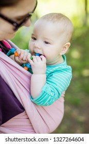 Young woman carrying her baby daughter in woven wrap outdoors in spring park. Baby girl chewing teething beads, mother looking at her with affection.