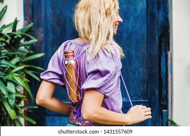 Young woman carrying reusable organic no-plastic copper bottle knitted with wearable handles