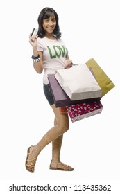Young woman carrying shopping bags and a credit card
