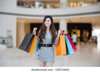 a young woman carrying shopping bags and smiling in mall