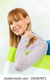 Young woman carrying shopping bags on her shoulder