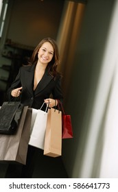 Young woman carrying shopping bags, smiling