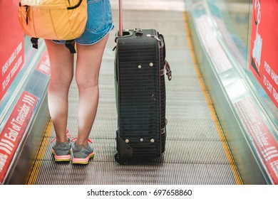 A young woman is carrying a suitcase on a moving walkway to purchase tickets to travel abroad at the airport.