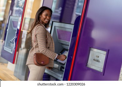 young woman at the cash machine looking happy
