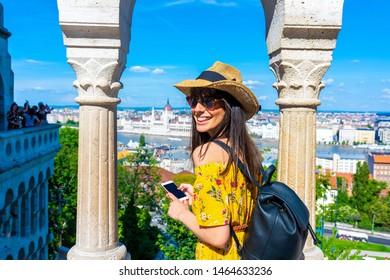 A young woman in the Castle of Budapest in Hungary taking pictures of the city with her phone.
