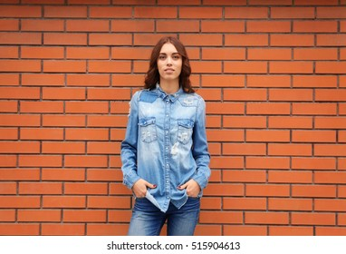 Young woman in casual clothes standing against brick wall