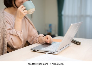 Young woman in casual clothing using laptop and drinking hot beverage while working from home