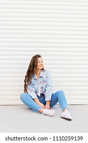 Young woman in casual denim outfit outdoors by garage door chilling out and smiling. Natural lighting, no retouch.