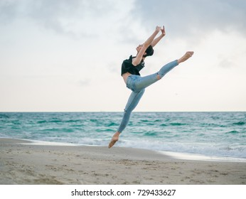Young woman in casual style - denim and black top doing ballet at the beach. Attractive ballerina practices in jumping on sandy coastline in autumn. Copy space