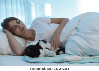 Young woman and cat in bed with electric heating pad, focus on cable