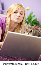 Young woman with cat at the laptop