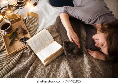 Young woman with a cat  lying in bed at home.  Winter or autumn weekend concept.