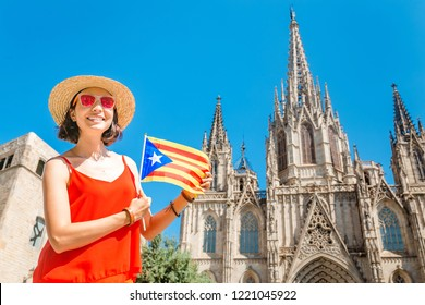 Young woman with Catalan flag in front of the famous Barcelona Eulalia Cathedral, Travel in Spain concept
