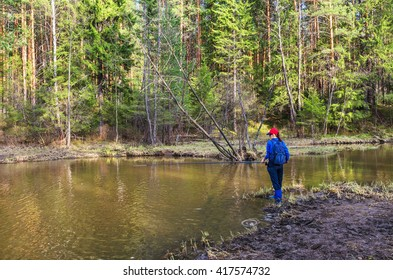 A young woman catches a fish in early spring on a small river. Looking into the camera