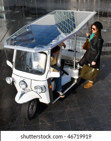 Young woman catching a ride in a solar powered tuc tuc