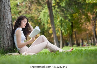 Young woman caucasian asian leaning against a tree and sitting in the grass reading a book in the park