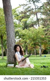 Young woman caucasian asian with long curly hair laying on grass against a tree writing in the park