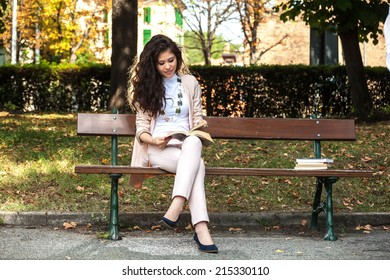 Young woman caucasian asian smiling and sitting on a bench reading a book in the park