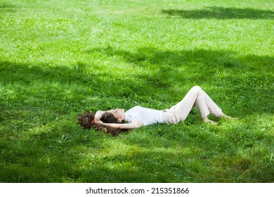 Young woman caucasian-asian relaxing laying on the grass in the park
