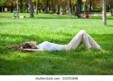 Young woman caucasian-asian resting laying on the grass in the park
