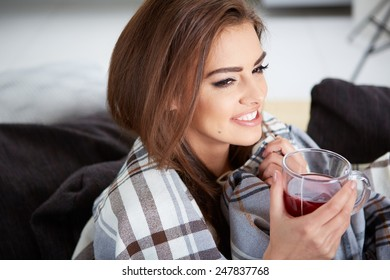 A young woman caught a cold covered with woolen plaid blanket